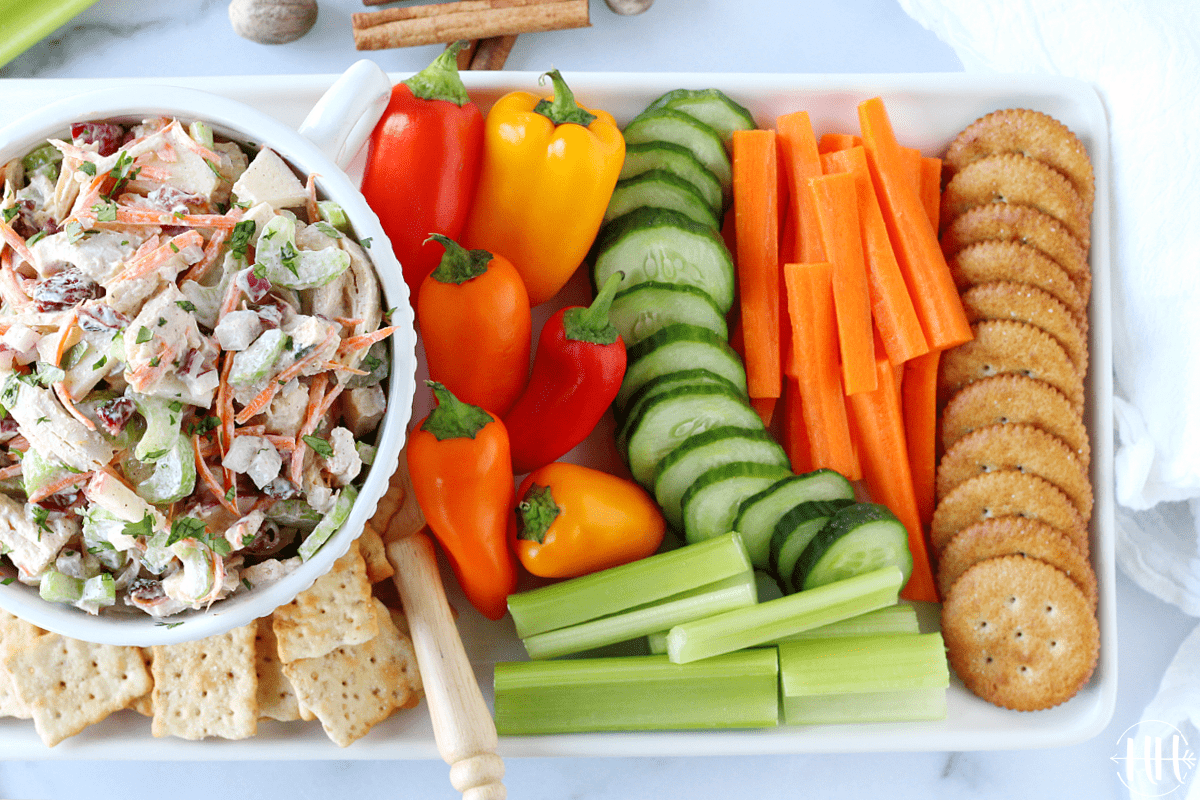 A white platter full of crackers, vegetable sticks, and turkey salad with dried cranberries.