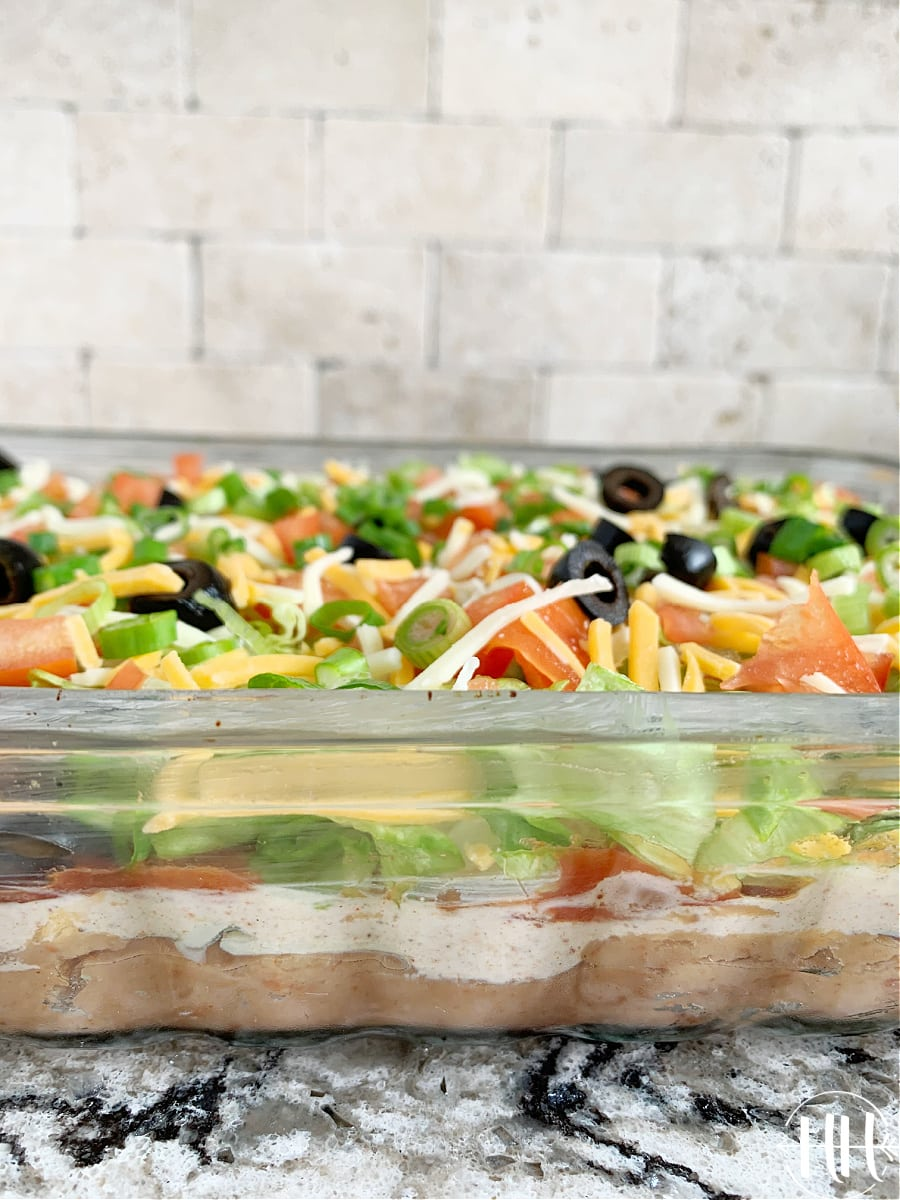 9 Layer Mexican Dip in a glass pan on a pretty countertop.