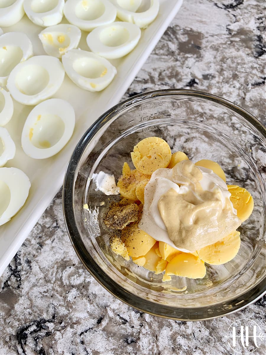 Hard boiled egg whites on a tray and the yolks and other ingredients in a bowl ready to be mixed.