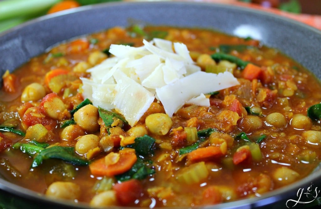 A bowl of Vegetarian Moroccan Chickpea Stew topped with shaved Parmesan cheese.