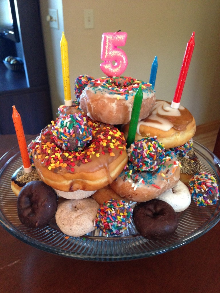 A cake made of stacked donuts for a 5th birthday.