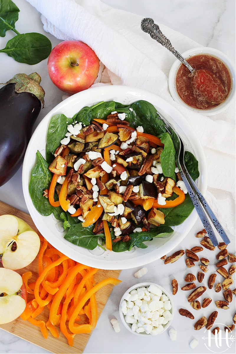 Salad loaded with bell pepper, crumbled goat cheese, and roasted veggies in a white bowl.