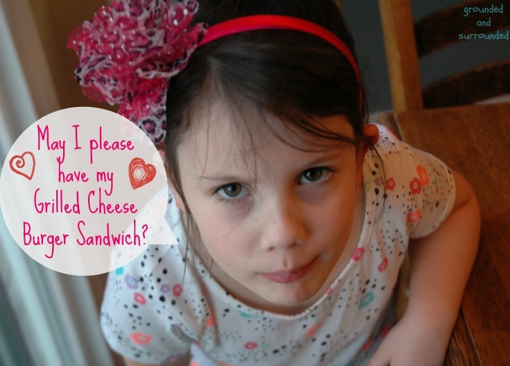 A little girl asking for her leftover grilled cheese burger sandwich.