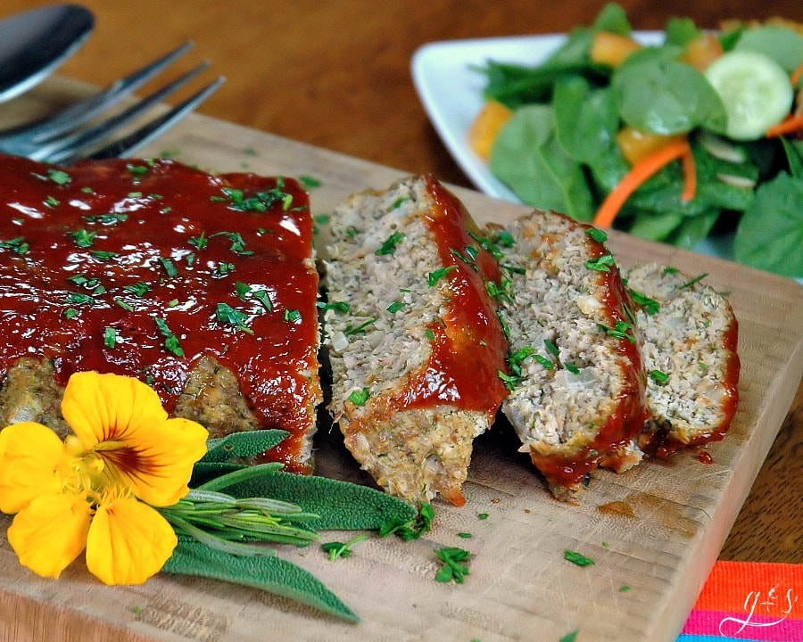 A meatloaf glazed with ketchup and chopped parsley on a cutting board.