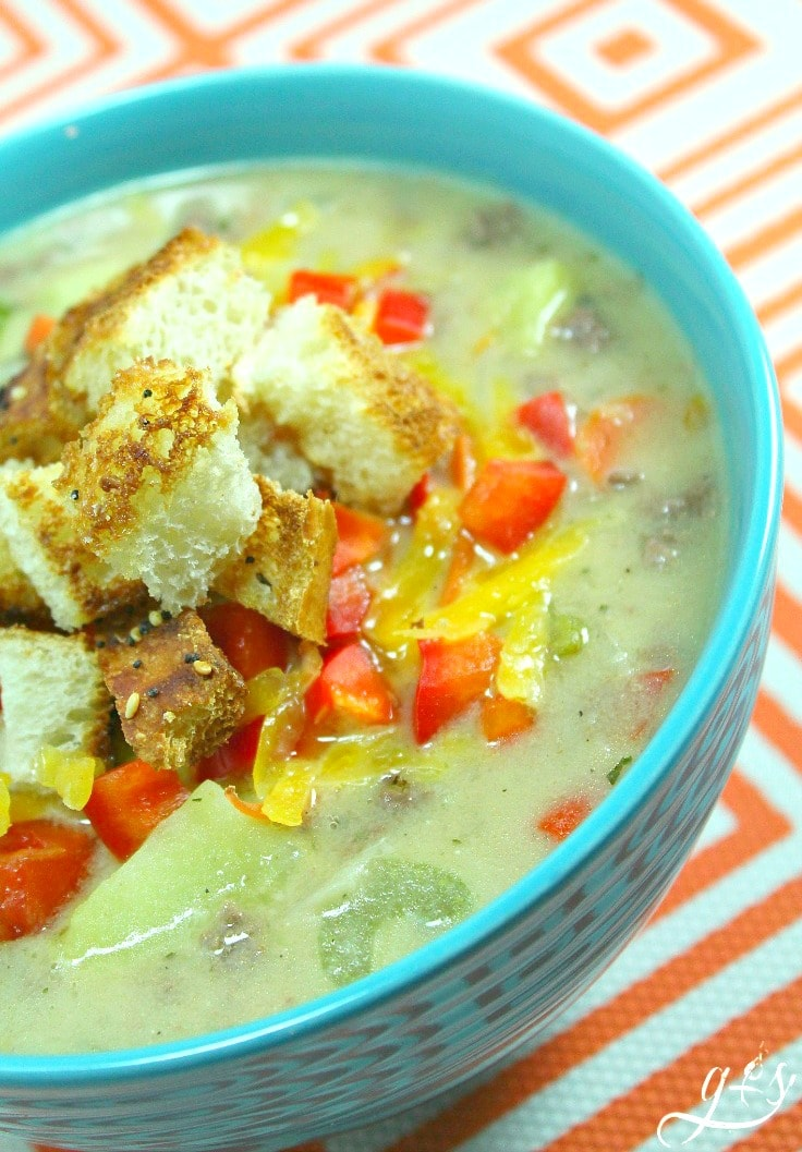 A turquoise bowl filled with Whole Foods Family Recipes: Cheeseburger Soup topped with homemade croutons.