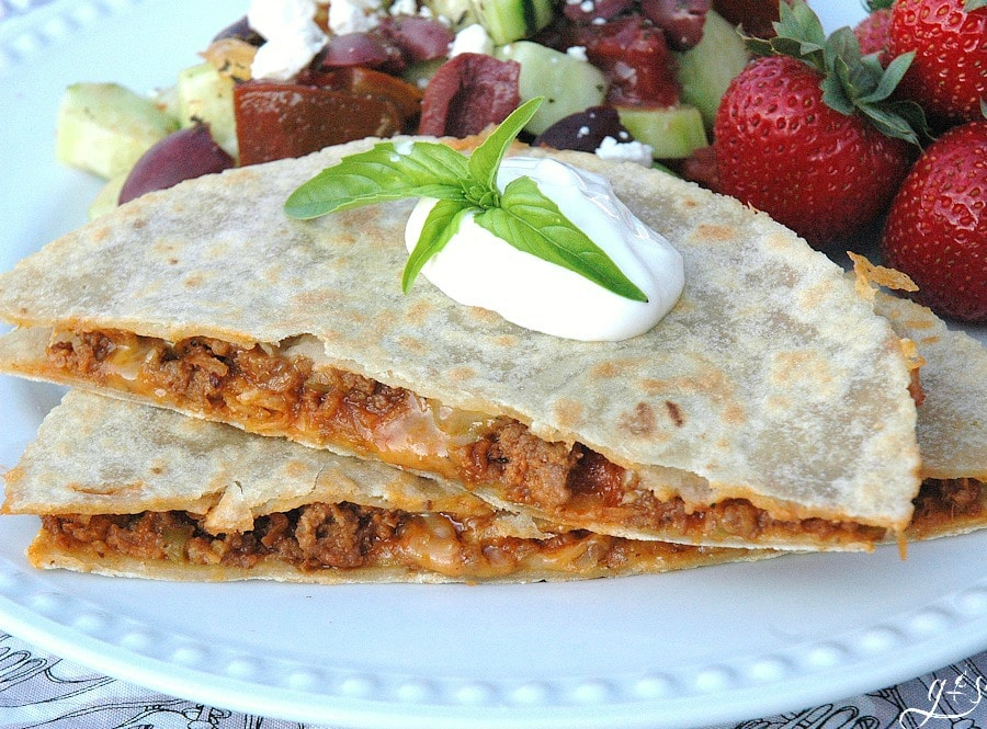 A sloppy joe quesadilla cut in half and stacked topped with sour cream.