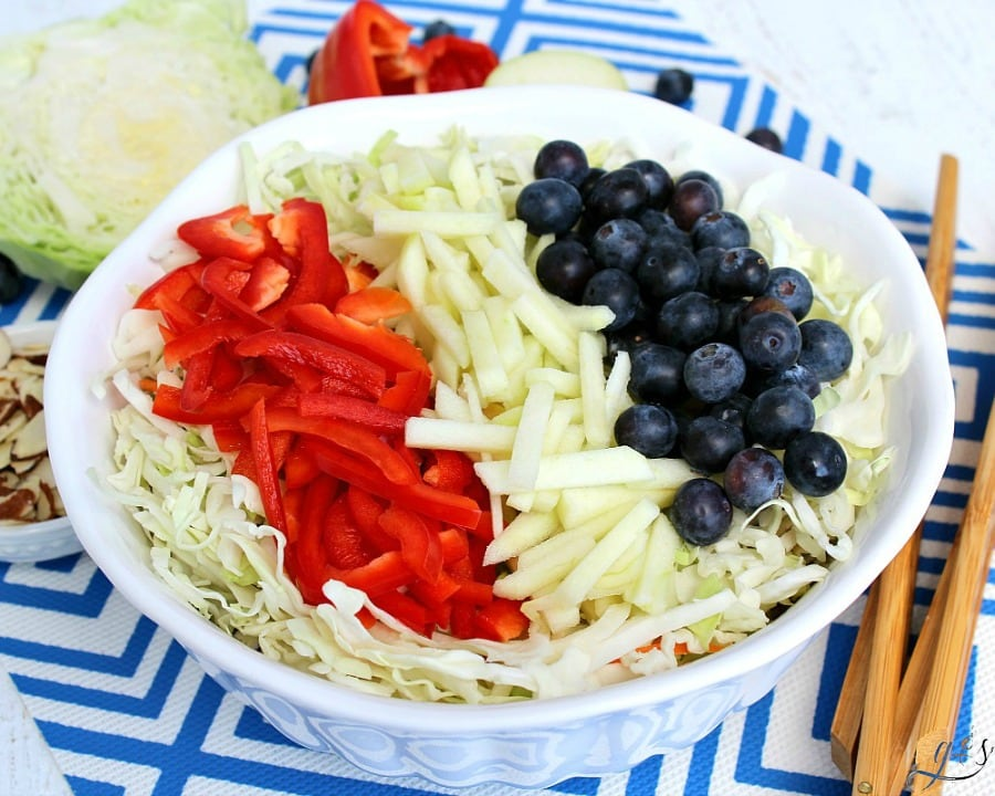 Red, White & Blue Slaw Salad in a beautiful white bowl ready to be served at the next July 4th, Memorial Day, Labor Day BBQ.