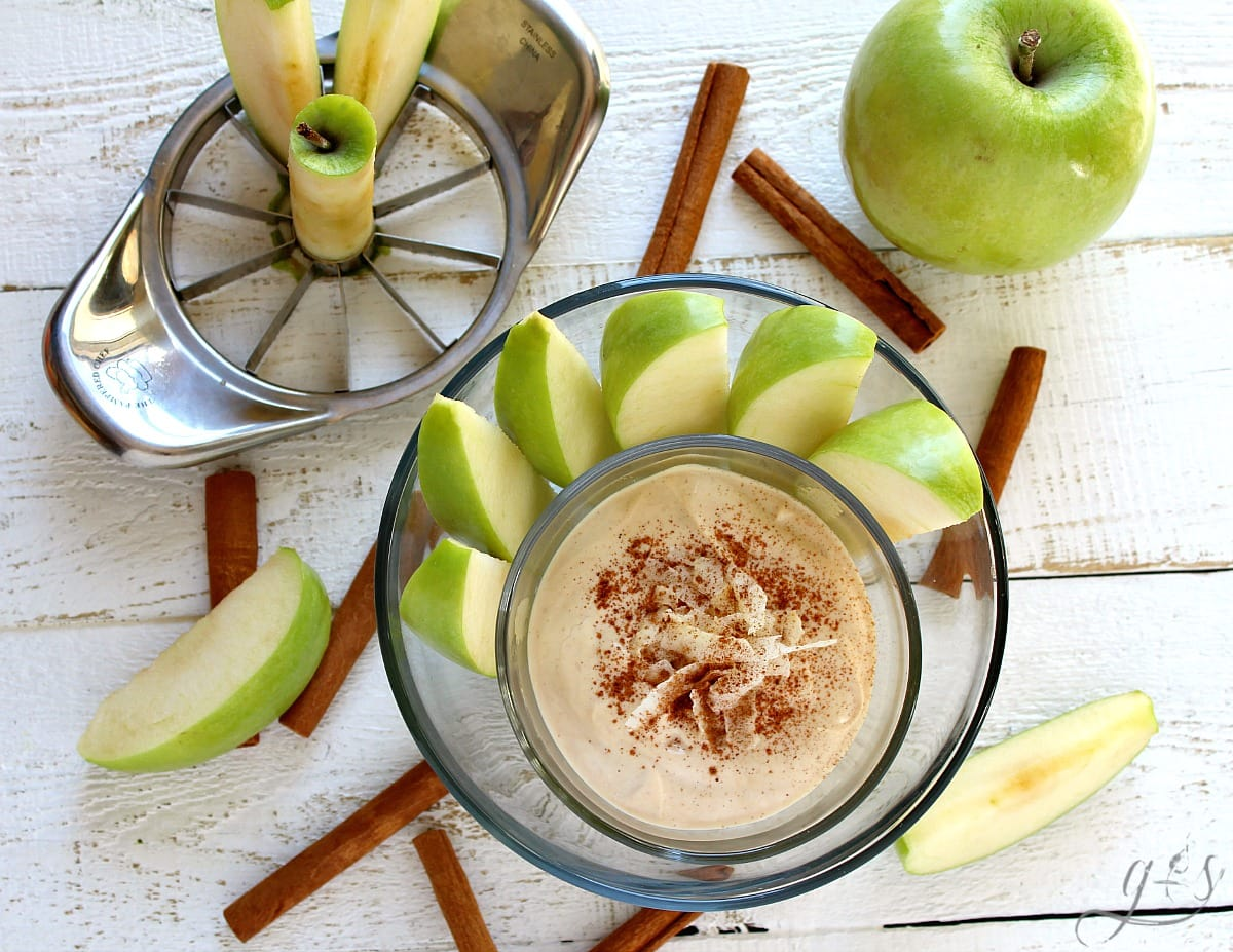 Powdered peanut butter mixed with plain Greek yogurt surrounded by cinnamon sticks and Granny Smith apples.