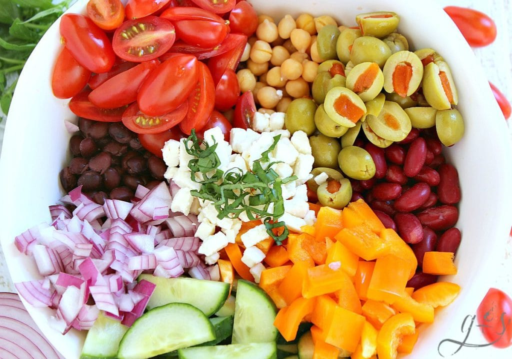 All the ingredients in a Mediterranean Tri-Bean Saladin a white bowl.
