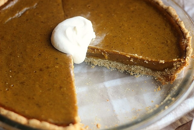 A gluten free Clean Honey Pumpkin Pie from Oatmeal with Fork with a dollop of whipped cream.