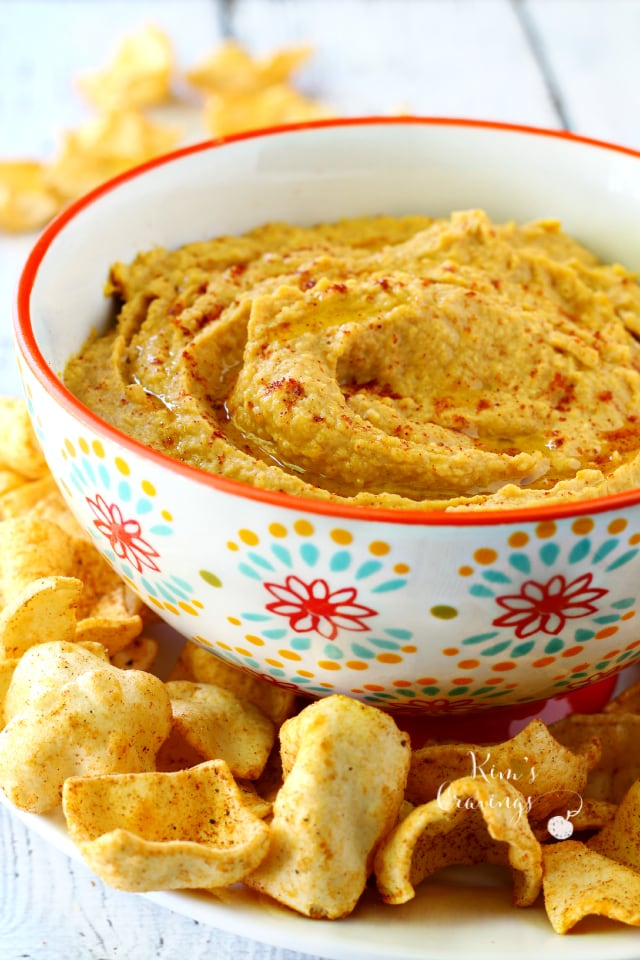Stunning orange Pumpkin Hummus from Kim's Cravings in a white flowered bowl.