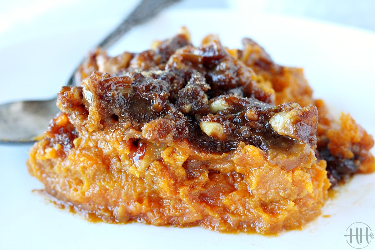 Vegan sweet potato casserole with candied pecans on a white plate.