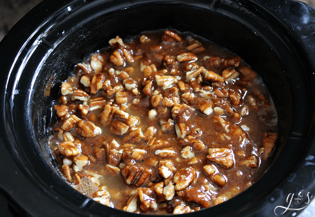 Small crock pot with a sugary layer of pecans on top ready to cook.