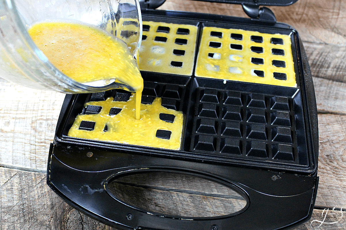 Pouring a cheesy egg mixture in a waffle iron.