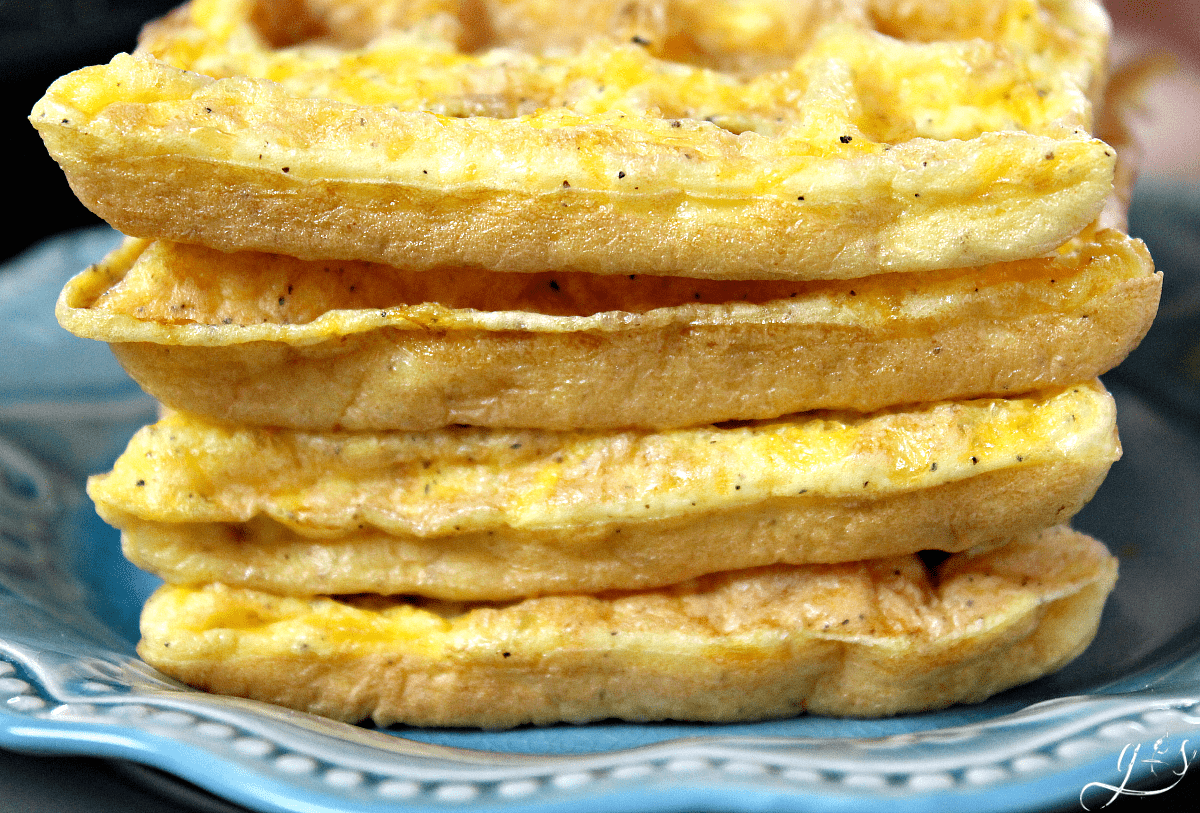 Fluffy clean eating egg waffles stacked on a blue plate.
