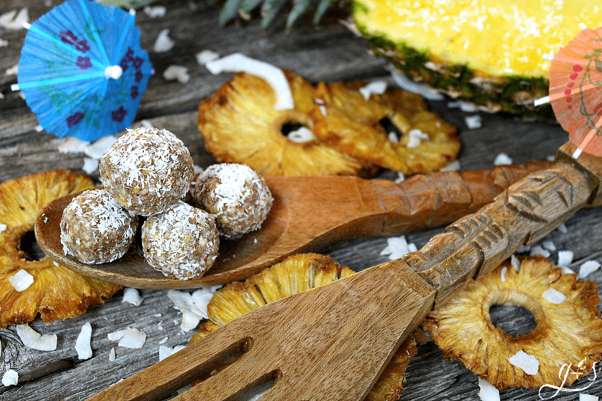 The BEST 4 Ingredient Pina Colada Energy Bites | This easy no bake recipe will become your favorite healthy snack, they taste just as dreamy as the cocktail drinks! Gluten-free dried pineapple, almonds, coconut, and vanilla combine to create a clean eating, Paleo, 21 Day Fix & Whole30 approved, and vegan non-alcoholic recipe that is perfect for kids and adults alike. Take on your next trip to the beach, hike, or pack for lunch! If serving only adults, add a little rum to the mixture!