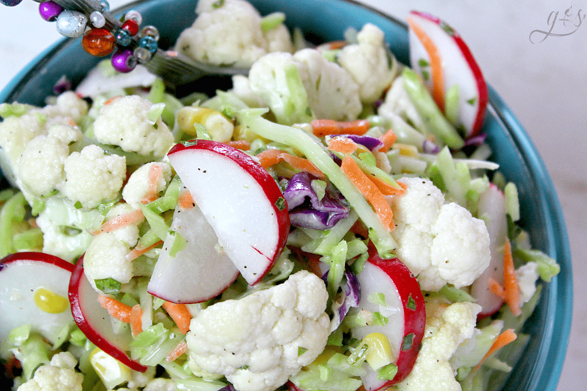 The BEST Cauliflower & Broccoli Slaw Salad | Say hello to the newest healthy and gluten free salad and homemade dressing recipes on the block! Add fresh radish and corn(fresh or frozen) to the main ingredients. Then a little clean eating mayo, fresh chopped basil, and a couple other easy pantry ingredients to the sauce. Eat this as a vegetarian meal for dinner and lunch or to feed a crowd. Spring and summer are my favorite seasons to eat this low carb and vegan side salad!