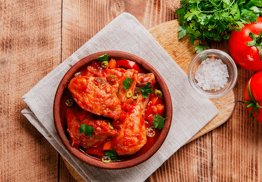 A Chicken & Tomato Chakhokhbili stew in a bowl garnished with green onion and parsley.