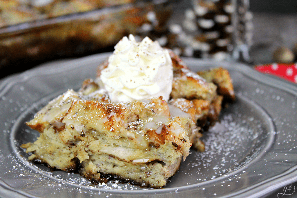 French toast bake with whipped cream on top on a grey plate.