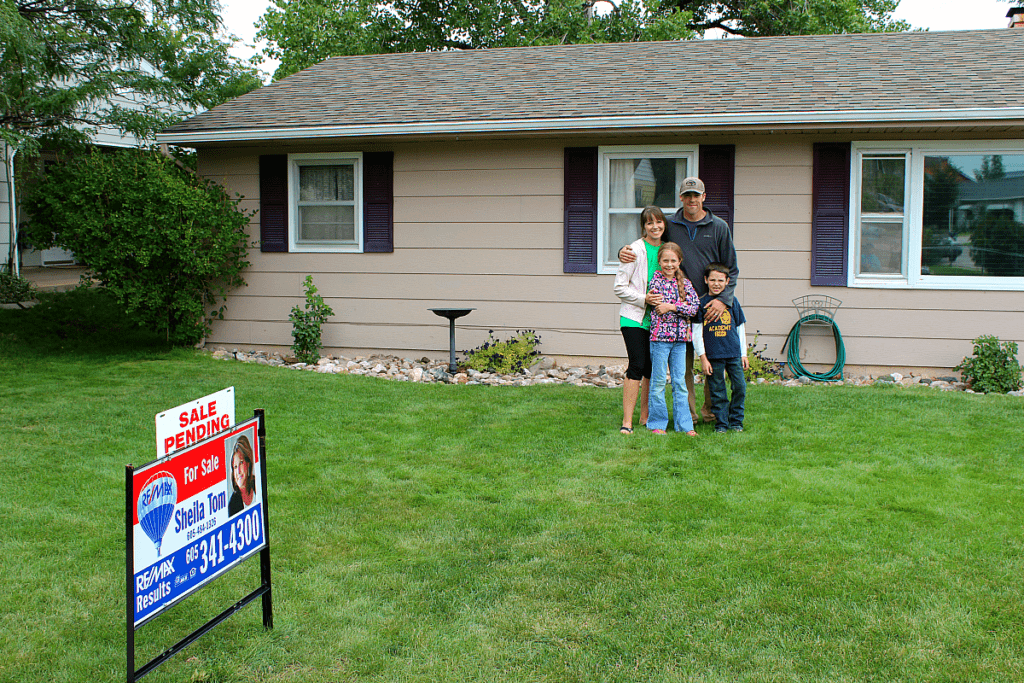 Family of four standing in front of their first home with a for sale sign in front of it. The home is tan with white trim and eggplant colored shutters.