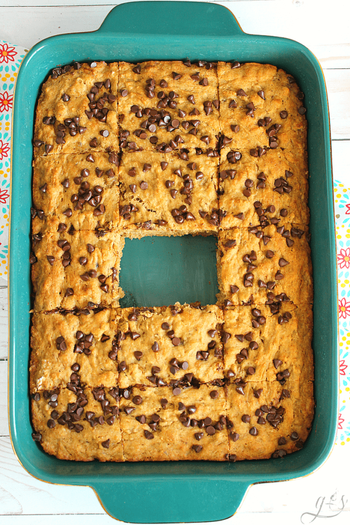 9x13 pan of banana bread blondies topped with mini chocolate chips and one bar missing from the middle.