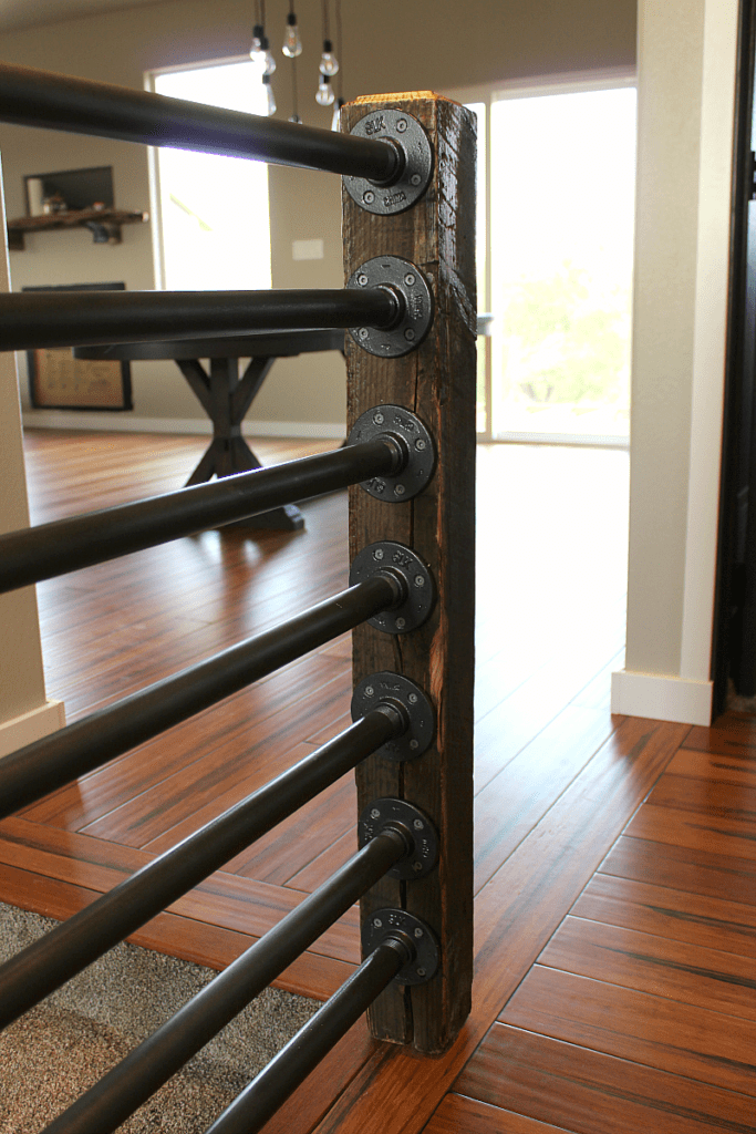 Rustic newel post made of reclaimed wood post and black metal steel pipe and flanges.