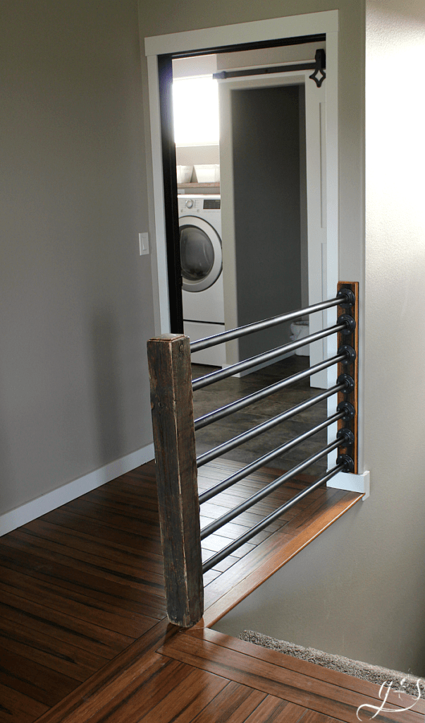 How to Build Your Own Banister | Building a beautiful rustic and industrial inspired stair banister is as simple as 1-2-3. Use iron or black steel pipe, a unique wooden post (reclaimed) for newel post, and some fittings. Whether your home is classic, contemporary, or new build this antique looking banister fits well. We built this inside, but the same stairway and railings concept can be used on the porch outdoors. #farmhouse #DIY #decor