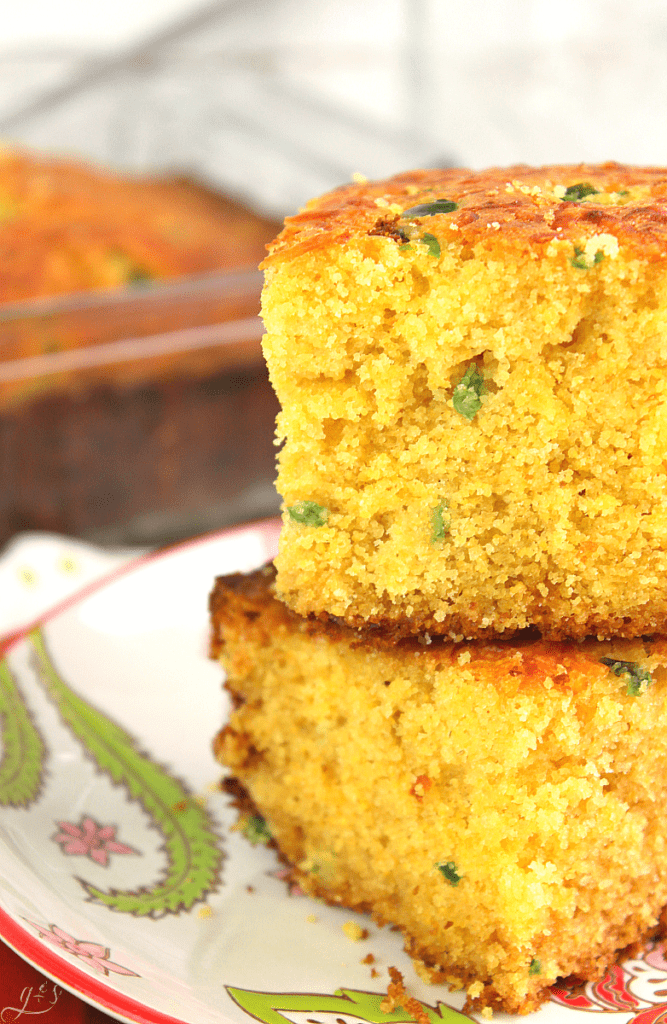 Detailed photo of Cheesy Jalapeno Cornbread showing specks of diced jalapeno and browned cheddar cheese on top.