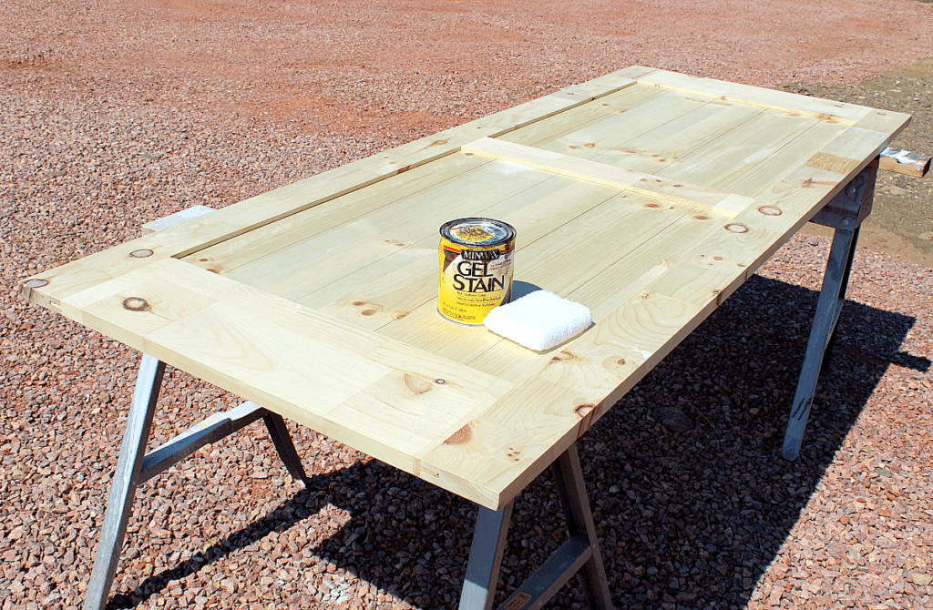 Gel stain container and cotton stain applicator sitting on untreated barn door.