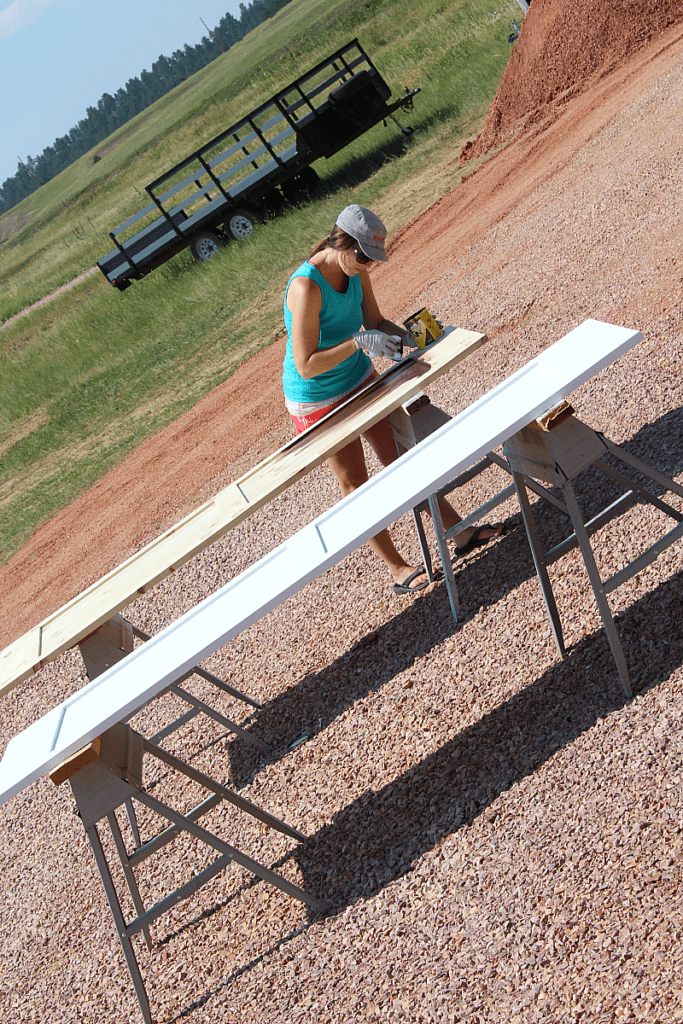 A white barn door and stained barn door with girl applying stain outdoors.