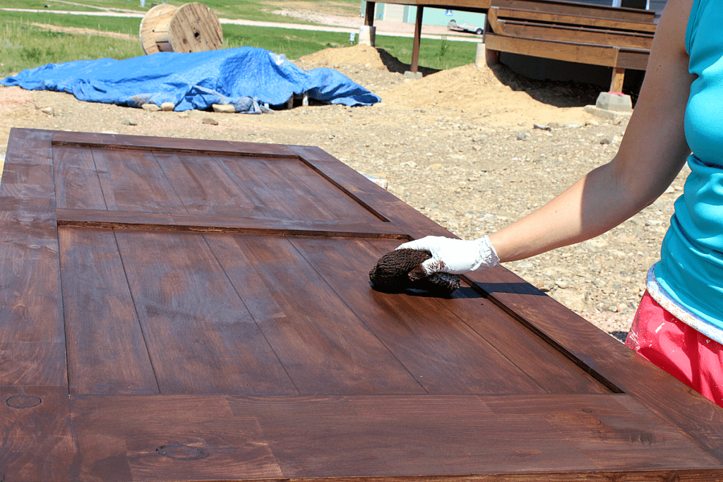 Applying gel stain with cotton pad on barn door.