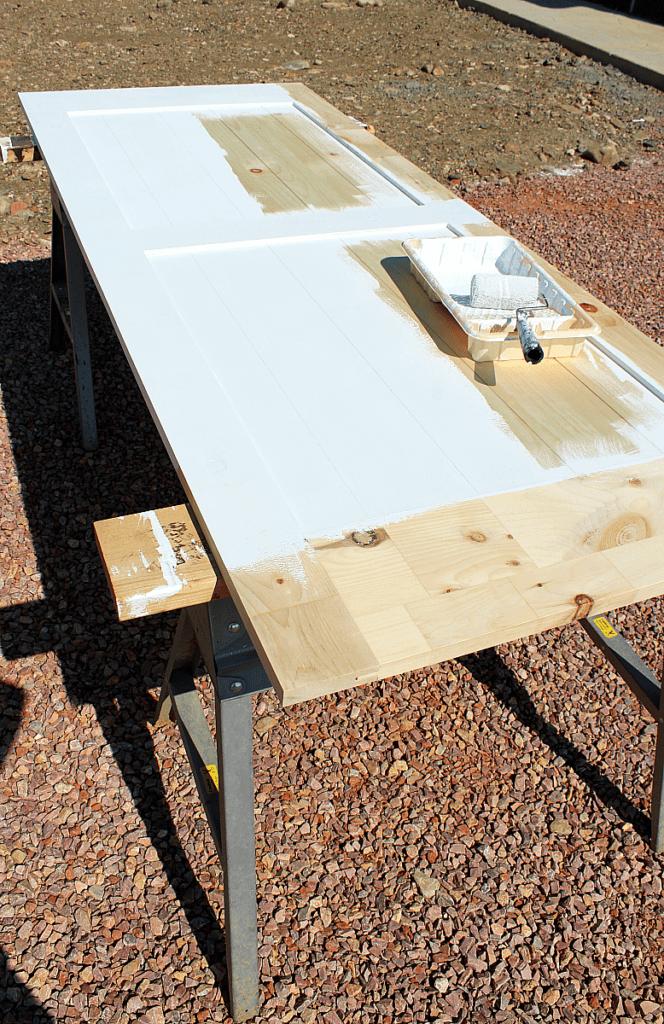 4 inch roller applying white chalkboard paint to barn door.