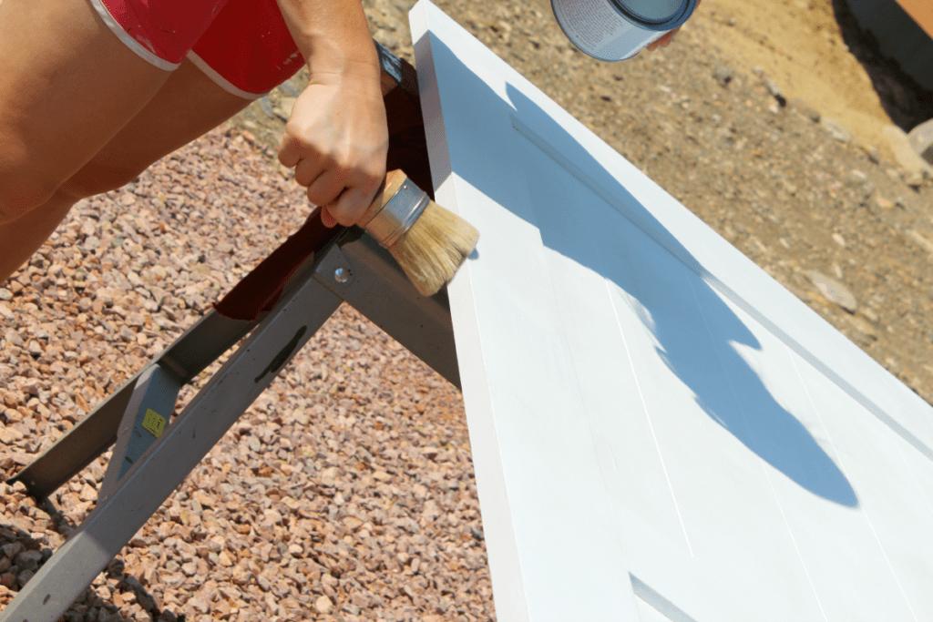Applying Annie Sloan clear wax to seal a white chalkboard barn door.