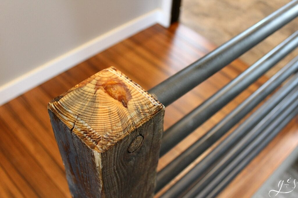 The top of a reclaimed wood post for an industrial stair banister.