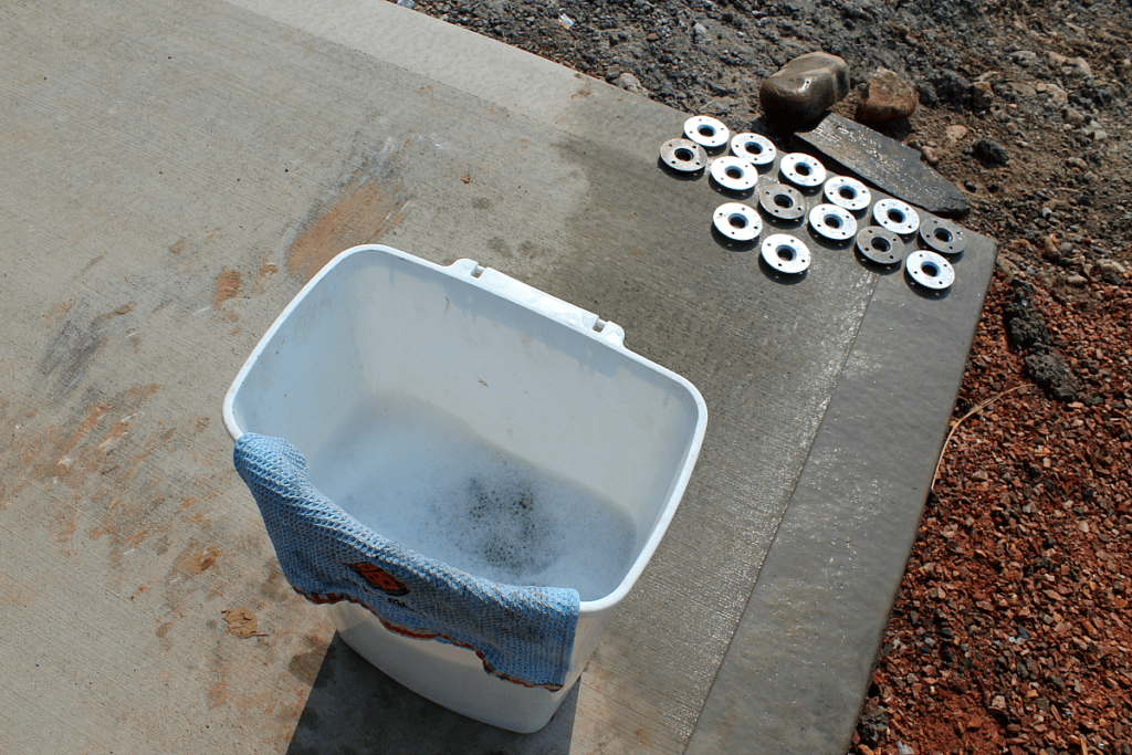 Garbage can full of warm water and soap to wash grease and oil off of steel railings.