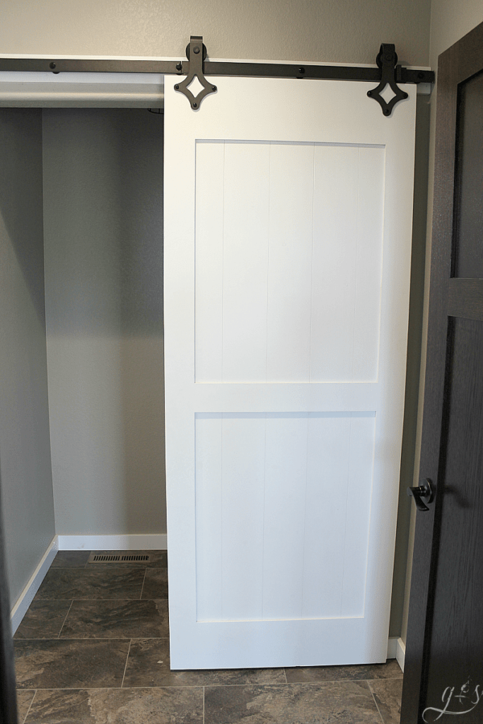 DIY Painted Barn Doors | We chose to hang two barn doors in our new home, one chalk board painted and one gel stained. You can do this project on the cheap with this tutorial. These sliding doors in our master suite and laundry room are modern yet rustic and farmhouse yet classic. The black industrial hardware and quiet floor guide work incredibly well. Plus they add so much style on a budget! #bathroom #bedroom #homedecor