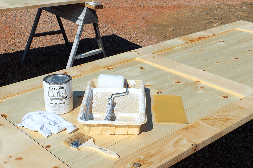 White chalk board paint, roller, brush, sand paper, rag atop barn door.