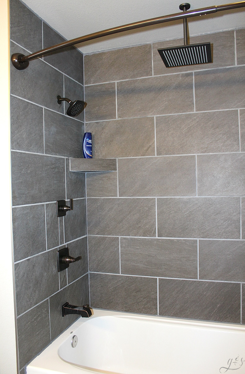 DIY How to Tile a Shower Surround with Tub | This master suite bathroom is spacious and luxurious. These grey ceramic tile ideas and designs are simple and beautiful for a remodel or new home build. This tutorial to install your own large tile on a budget will make you feel like a professional! Plus, we show you how to make gray shelves to hold your items and enjoy that rainfall shower head.