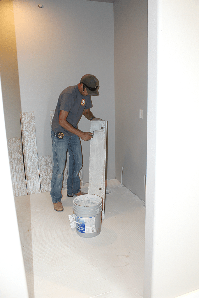 Man applying mortar to a long tile to place on bathroom floor.