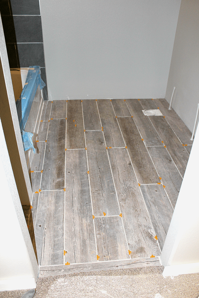 "Photo of completed tile floor planks in bathroom with 1/4"" spacers."