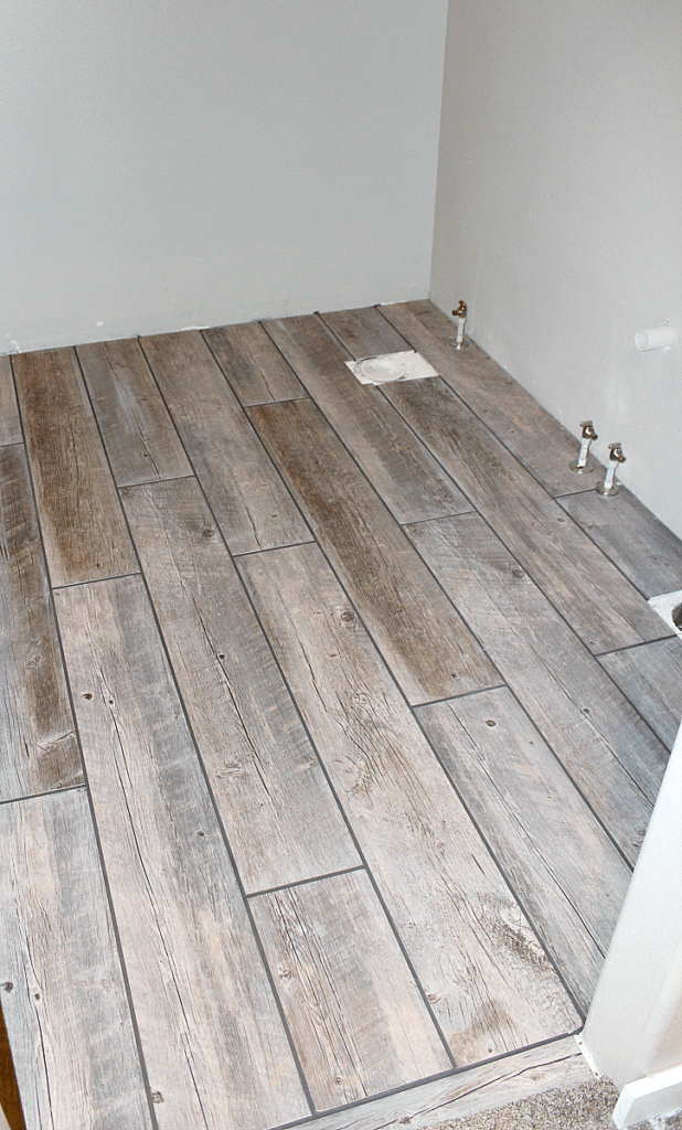 Wet grout lines in dark pearl grey between long porcelain tile planks in bathroom.