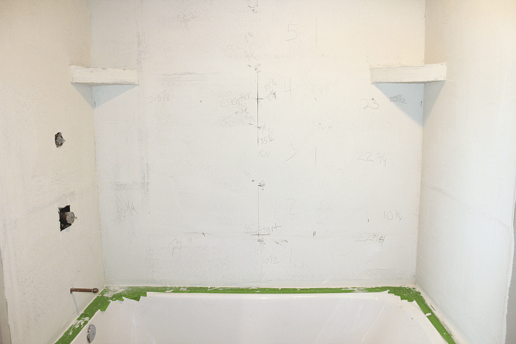 White cement board walls with pencil markings for installing ceramic tile.