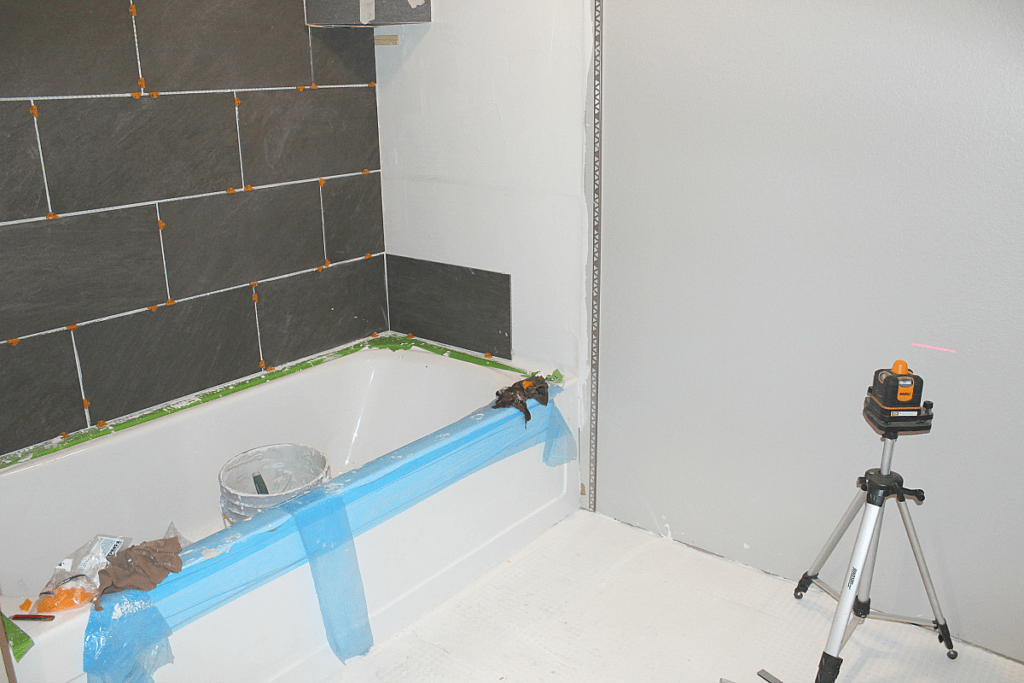 Laser level in bathroom helps ensure level tile placement.