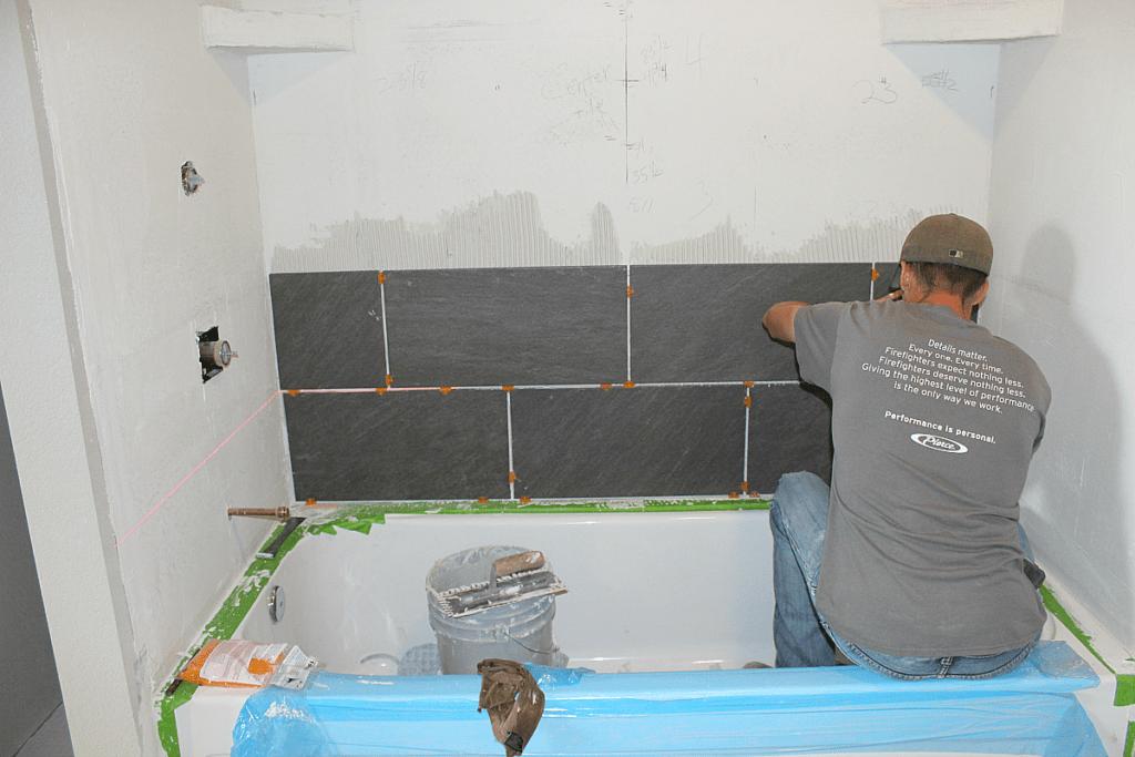 Man installing grey tile in shower surround.
