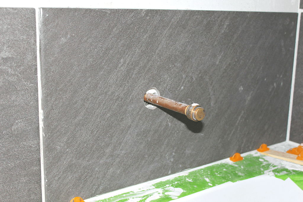 Copper pipe extending through hole in ceramic tile in a shower.