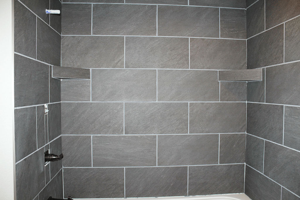 Almost finished tiling in tub surround. Large grey tiles grouted with Pearl Gray sanded grout.
