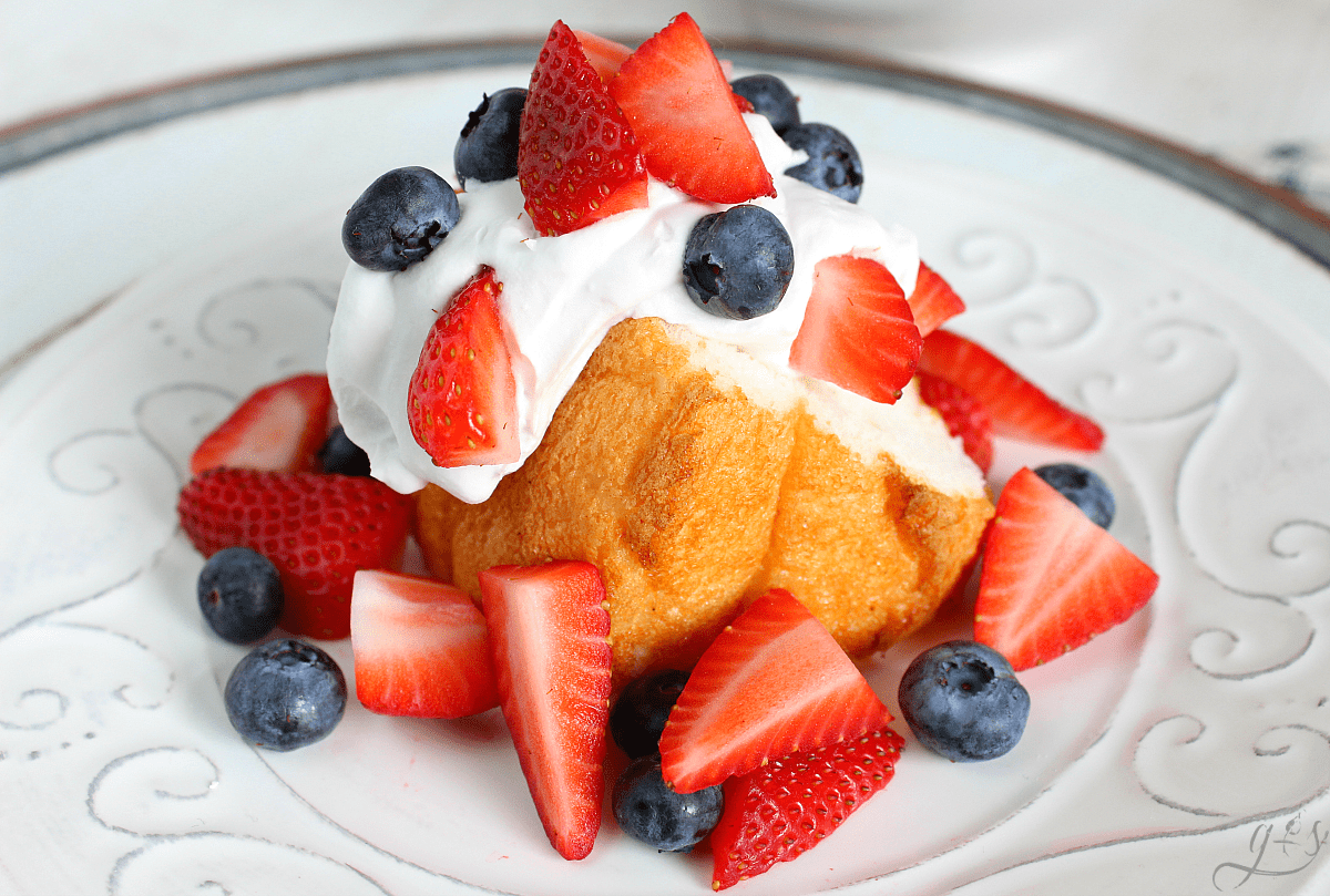 Patriotic Shortcake on a white plate complete with angel food cake, berries, and coconut whipped cream.