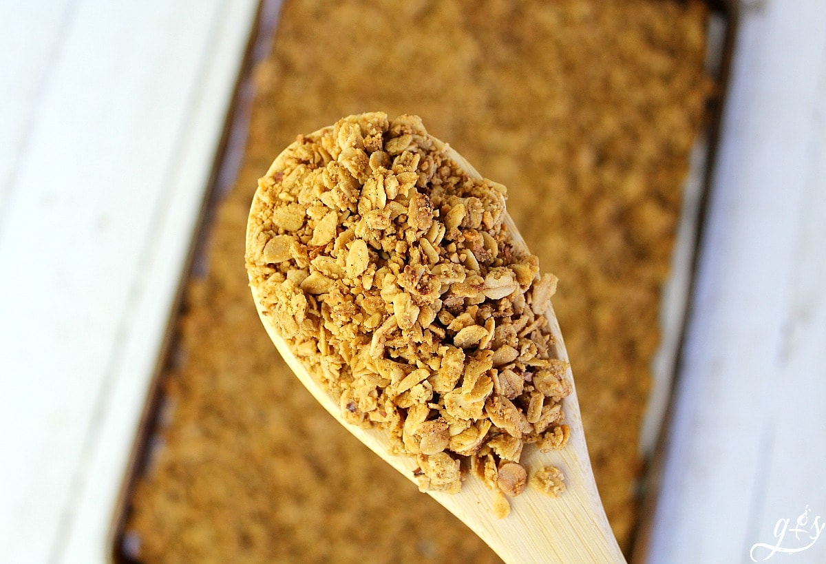 Wooden spoon full of French Toast Granola held over the pan of warm granola.