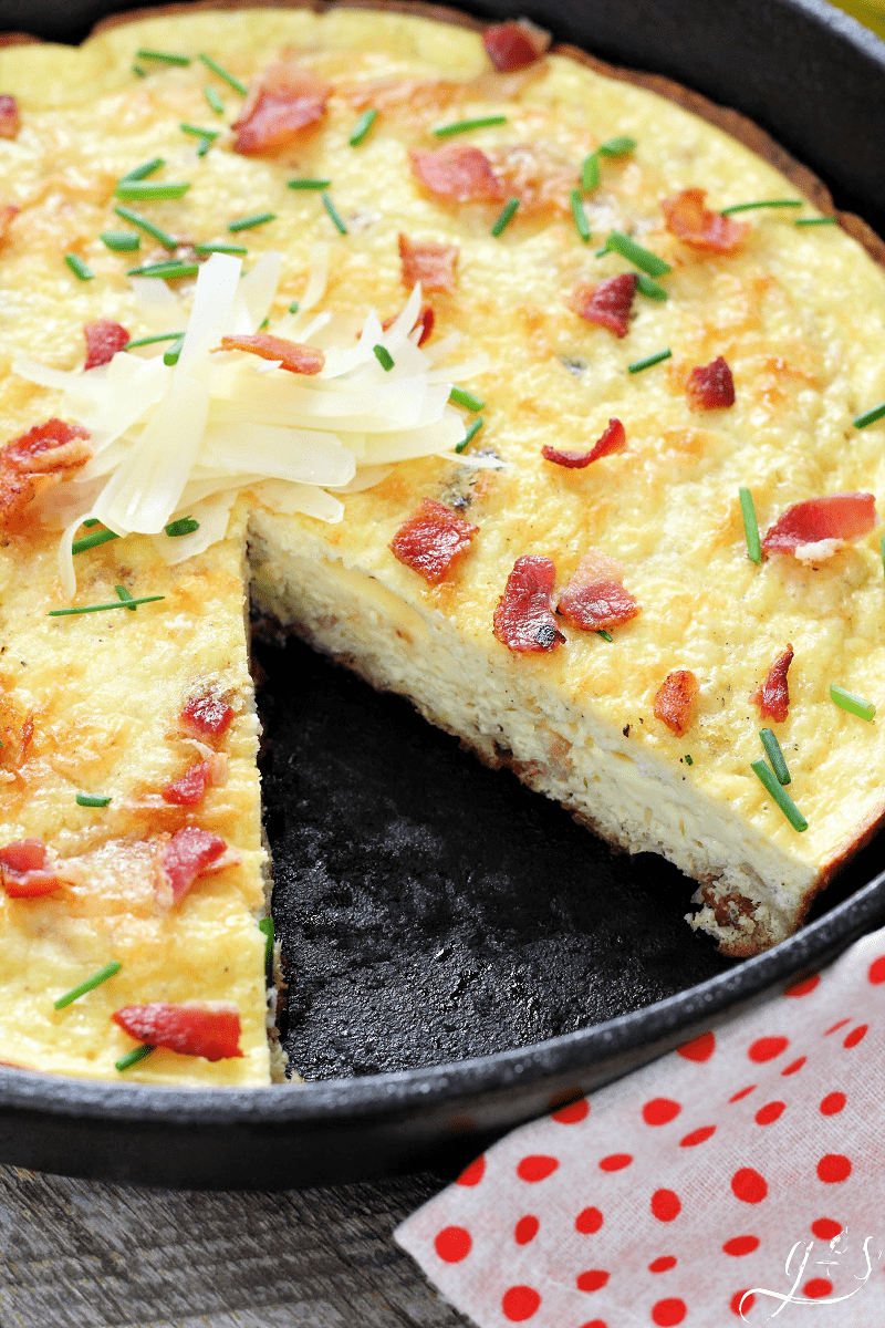 Gorgeous portrait photo of frittata garnished with chopped bacon, chives, and Parmesan shavings.