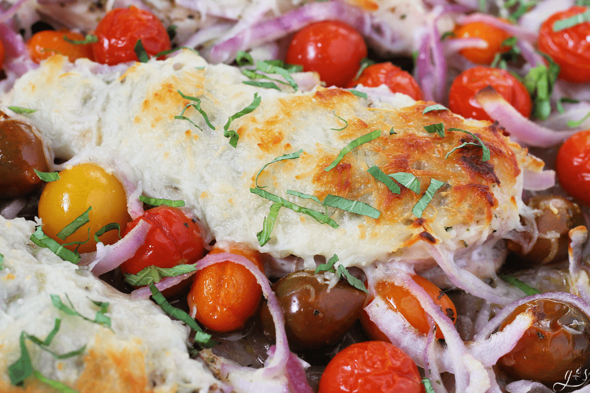 Up close photo of baked chicken breasts covered with browned mozzarella cheese and chiffonade basil. Colorful cherry tomatoes and red onion surround the chicken.